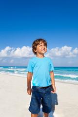 Cute kid standing on the sandy beach of  seashore