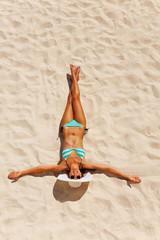 Tanned young woman in bikini on beach sand