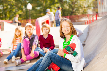 Girl sits in front with skateboard and other kids