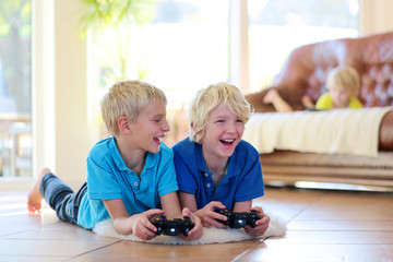 Two boys playing video games at home