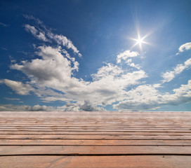 wood stage under blue sky with clouds