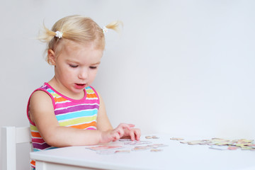 Toddler girl assembling jigsaw puzzle