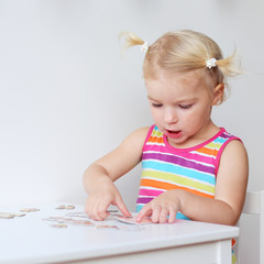 Toddler girl assembling jigsaw puzzle