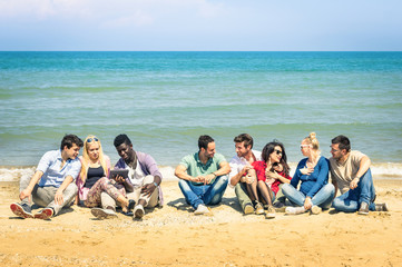 Group of multiracial best friends talking at the beach