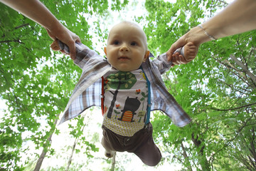 Dad playing with baby flying tosses summer