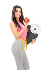 Woman holding a weight scale and an apple