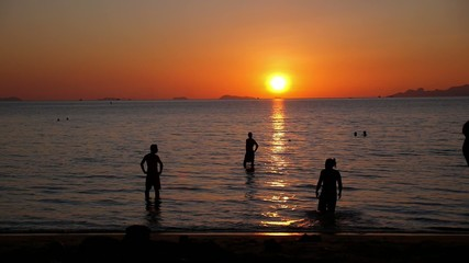 Young People Swimming in Sea at Beach on Beautiful Summer Sunset