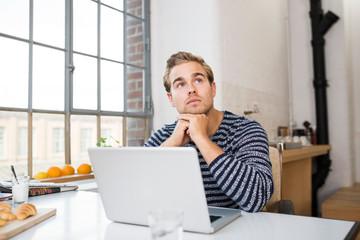 junger mann arbeitet zuhause am laptop