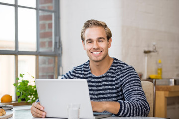 glücklicher junger mann am laptop