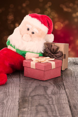 Santa Claus toy leaning against gift boxes