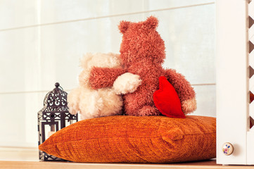 Two embracing teddy bear in love toys on window-sill