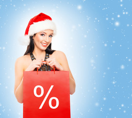 Young and beautiful Christmas shopper girl on a blue background