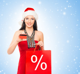 Young and beautiful Christmas shopper girl with a credit card