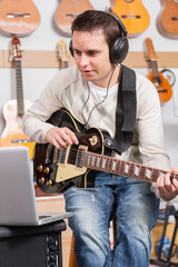 Man playing a guitar and recording her music in computer