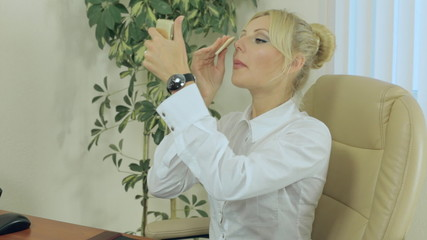 Beautiful blonde powder  her face at work in office