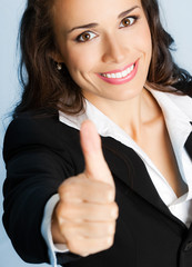 Businesswoman with thumbs up, over blue