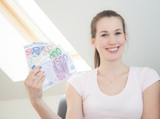 Attractive young woman holding lots of euro notes.