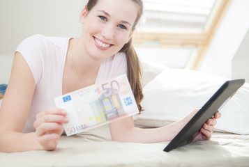 Attractive young woman holding 50 euro and tablet device