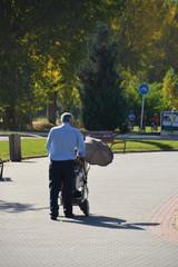 abuelo paseando con un carrito de niño