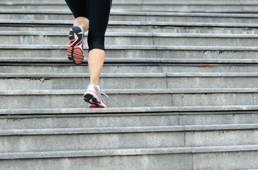 young fitness woman legs running up on stairs