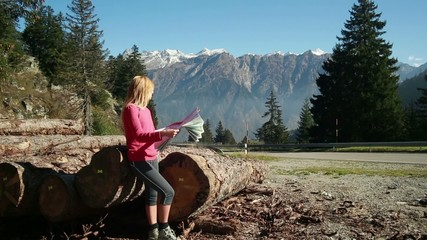 Woman reading a map beside mountain road