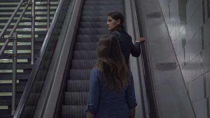 Businesswomen riding by escalator, slow motion shot, steadycam