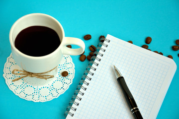 Overhead of notebook with pen and coffee