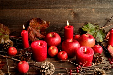 Red apples with candles on wooden background
