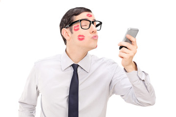 Man sending a kiss through a cell phone