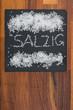 canvas print picture - Grobes Salz auf schwarzem Schiefer mit Holzhintergrund