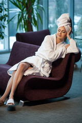beautiful woman in a bathrobe sitting with closed eyes