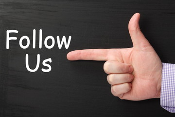 Follow Us with pointing finger on a blackboard