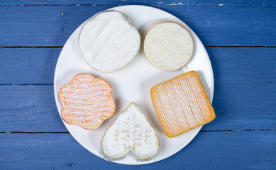 different French cheeses on a table blue wood