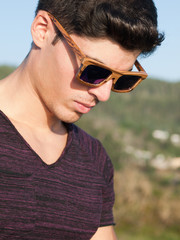 Model man portrait with wooden sunglasses outdoors