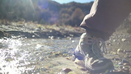 Close up on hiker's boots crossing mountain stream