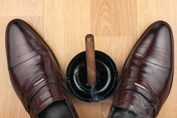 Classic men's shoes, ashtray and  fuming cigar on the wooden flo