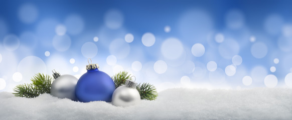 Weihnachtskugeln im Schnee vor Blau