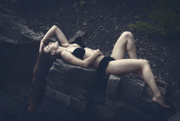 Beautiful brunette girl among the rocks. Toned in cold color.
