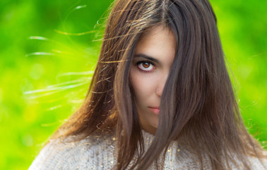 Portrait of young woman in sweater. Green bokeh background.