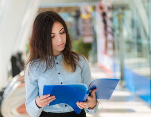 Young woman with blue folder in office. Selective focus.