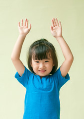 Excited asia little child raising two hand up