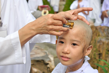 little girl be removed hair to become a nun during a Buddhist o