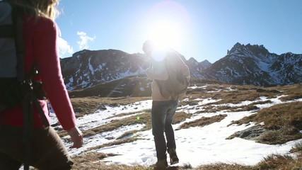 Hikers walking towards mountain peak, stops for a break