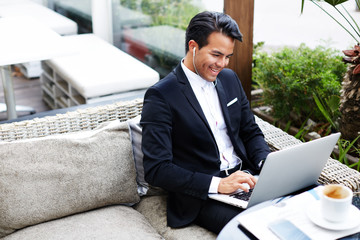 Happy handsome businessman looking at laptop computer screen