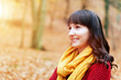 Pretty woman in read sweater smiling in fall autumn park