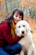 Young pretty woman hugging cute white dog in autumn fall park.