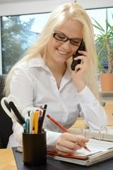 Bürokraft telefoniert am Schreibtisch