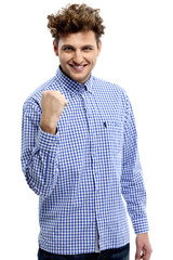 Portrait of excited young man clenching fists