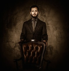 Handsome well-dressed  standing near leather chair