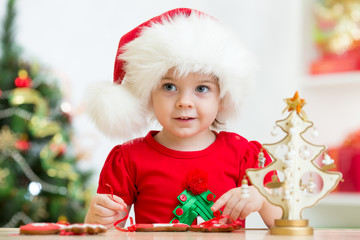 child girl in Santa hat making Christmas decorations